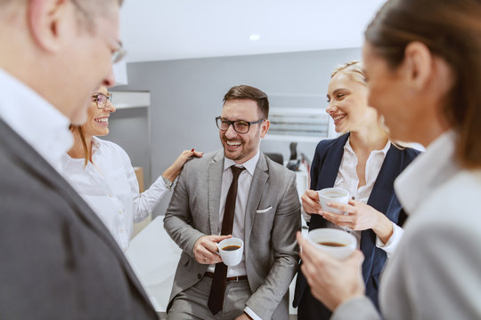 Group of smiling cheerful colleagues sitting and standing at workplace, chatting and drinking coffee on pause.