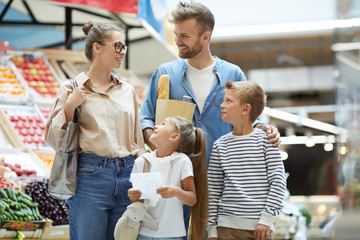 Portrait of contemporary family with two kids shopping at farmers market, copy space