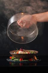 Tasty burnt caprese salad, cloche in hand, dark background.