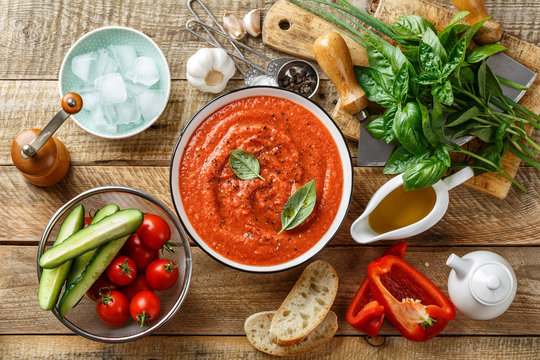 Gazpacho soup. Traditional spanish cold tomato soup of fresh raw vegetables with cooking ingredients on a wooden table top view