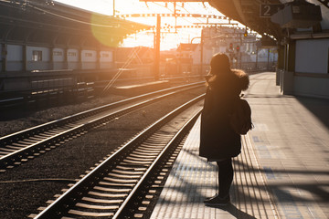 A woman is waiting the train at the station in Japan.