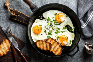 fried eggs in a cast iron pan top view