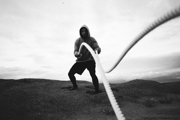 Strong fit athlete doing intens workout exercises using two battle ropes on outdoor. Alone sports man doing fitness workout at beach. Black and white color