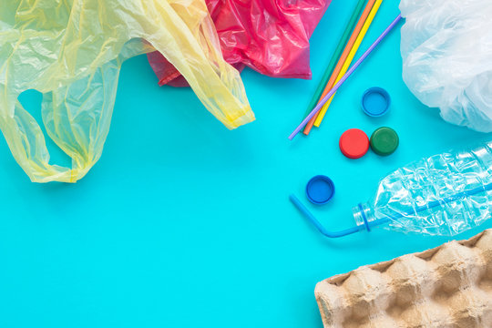 White single-use plastic bags and other plastic items on a yellow background. The concept of choice without plastic or environmental problems.
