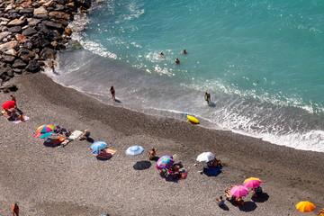 Playa de agua azul y arena negra, con sombrillas. Foto desde arriba.
