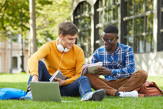 Full length portrait of two college students studying outdoors sitting on green grass in campus, copy space