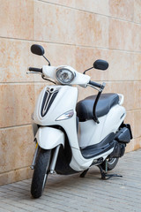 scooterModern scooter white, made in retro style, parked on the background of beige shell wall with anti-theft device.
