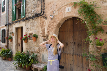 young woman tourist wearing summer hat sightseeing street in mediterranean town in summer season