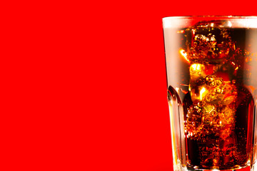 Coke with ice cubes closeup. Glass of fizzy brown drink over red background