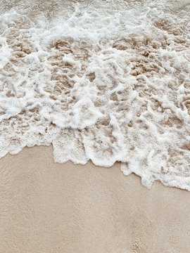 Beautiful tropical beach with white sand and sea with white frothy waves on Phuket, Thailand. Minimal composition with neutral colors. Summer and travel concept. Natural background.
