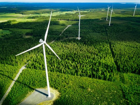Aerial view of windmills in summer forest in Finland. Wind turbines for electric power with clean and Renewable Energy
