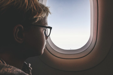 Boy with glasses looking clouds and sky outside the plane porthole. Teen have flight looking astonished in the airplane window.Child enjoy journey dreaming about future while travelling in airplane.