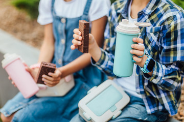 Close up photo. Breakfast time for children. Thermos and sweets cake on friends hands.