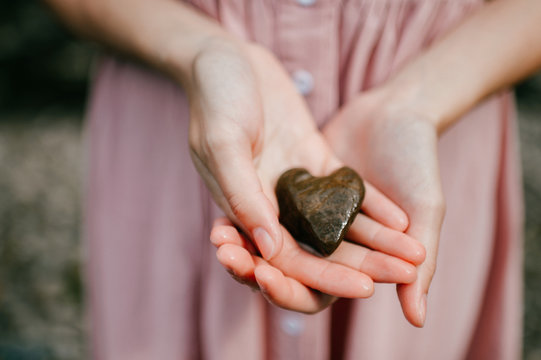 Female hands holding stone looking like heart