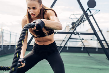 Woman doing fitness training using battle ropes on outdoors gym