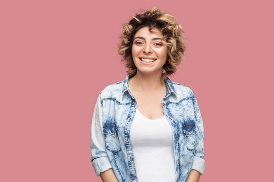 Portrait of beautiful happy young woman with makeup and curly hairstyle in casual blue shirt standing and looking at camera with toothy smile. indoor studio shot, isolated on pink background.