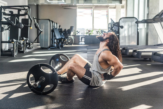 Portrait of injury young adult man athlete with long curly hair working out in gym, sitting on floor and have strong hurt problem with back, spasm painful. Gripping spinal with hand, screaming. Indoor