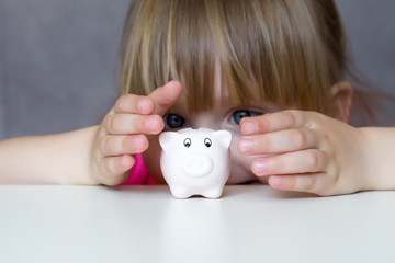 Little smile girl and piggy bank