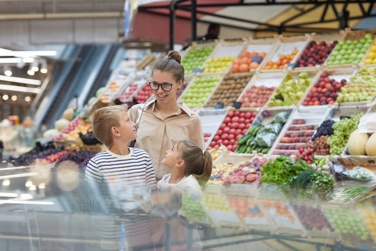 Portrait of contemporary young woman with two kids shopping together at farmers market, copy space