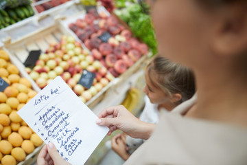 High angle closeup of unrecognizable young woman holding shopping list while buying groceries at farmers market, copy space