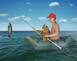The fisherman im a red cap with his cat is fishing in the rubber boat in the sea. They caught a big fish.