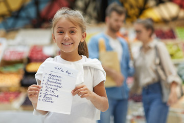 Waist up portrait of cute little girl holding shopping list and smiling at camera while buying groceries with family in supermarket, copy space