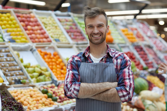 Waist up portrait of handsome young man working in supermarket and smiling at camera while posing by fruit stand, copy space