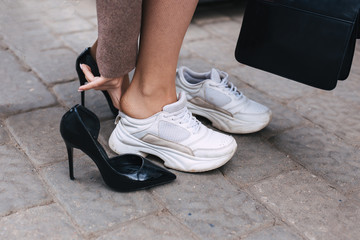 Barefoot business woman shanging shoes from high heel to comfortable sneaker