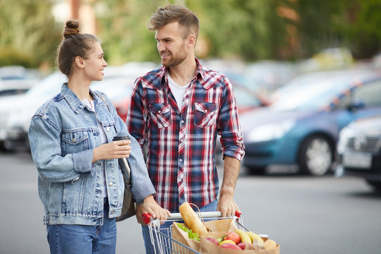Waist up portrait of contemporary young couple pushing shopping cart in parking lot after buying groceries, copy space