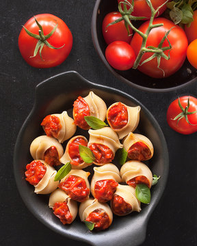 Stuffed large shells pasta with meat and tomatoes in sauce. Conchiglioni Italian cuisine. Copy space. the view from the top