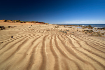 Western Australia - coast line at Dampier Peninsula with rippled sand dune and hill in the background in morning light