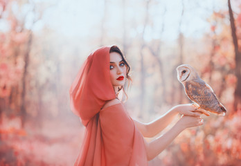 mystical pagan woman with covered head in peach scarf in forest, holds cute little barn owl. lady with dark curled hair, bright make-up and fair pale skin, daughter of autumn forest caring for bird Fototapete