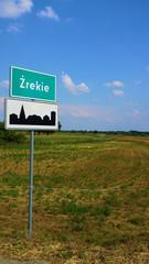 Fototapeta Znak drogowy w Europie na tle nieba i łąk z drzewami obraz