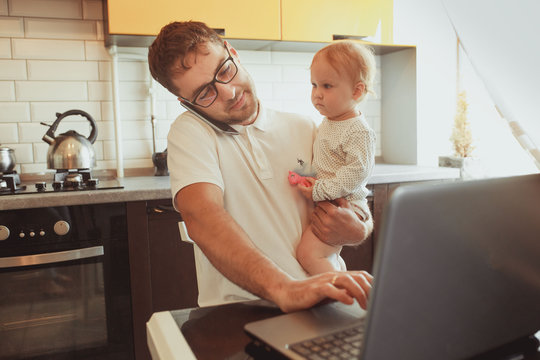 Father Working From Home On Laptop With Baby daughter