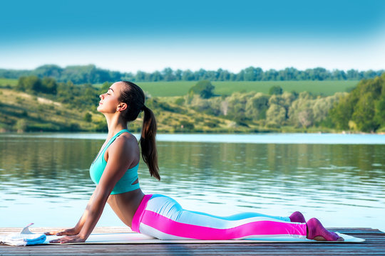 Yoga. Cobra pose.Beautiful girl in the pose of a cobra is engaged in yoga on the background of beautiful nature.Healthy lifestyle and wellness concept. Calm and relaxation, female happiness.