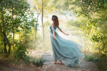 fairy-tale princess in light summer blue turquoise dress on wide path and walks towards wind, graceful dancing girl in image of flower with flying long hem of dress, nymph of bright green forest