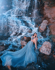 lost princess sitting on wet stones near gorgeous high waterfall, lady in blue dress with delightful long amazing train laid out on water, picked up legs and thought, fairy-tale daughter of aqua
