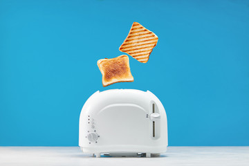 Roasted toast bread popping up of toaster with blue wall