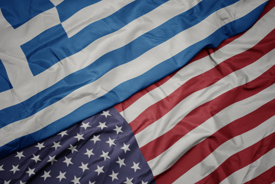 waving colorful flag of united states of america and national flag of greece. macro