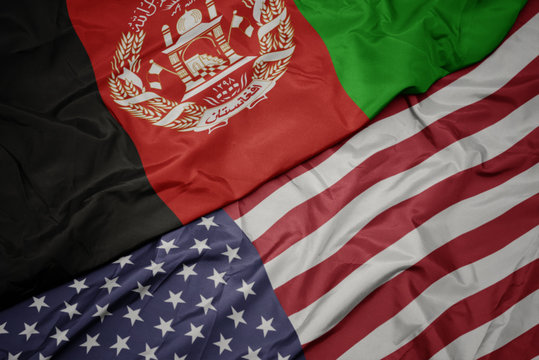 waving colorful flag of united states of america and national flag of afghanistan.