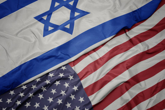 waving colorful flag of united states of america and national flag of israel.