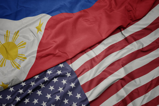 waving colorful flag of united states of america and national flag of philippines.