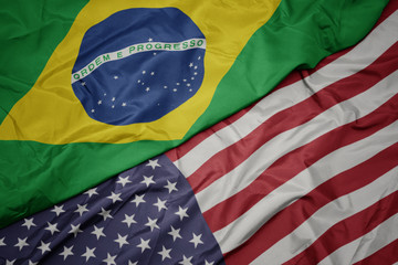waving colorful flag of united states of america and national flag of brazil.