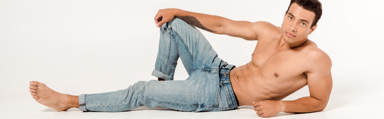 panoramic shot of handsome and shirtless man in blue jeans on white