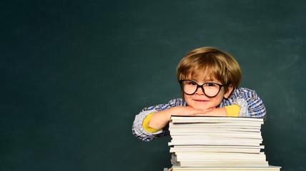 Funny little boy pointing up on blackboard. School concept. School kids against green chalkboard....