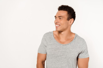 positive mixed race man in grey t-shirt smiling on white