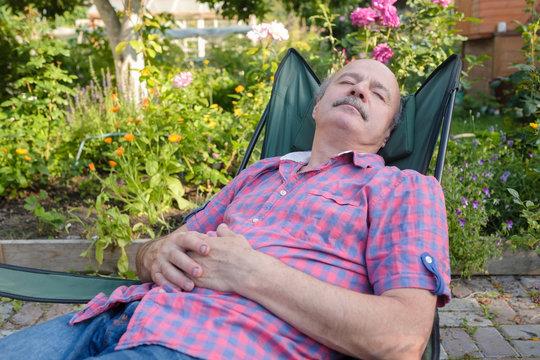 Man sitting leaning back on chair sleeping in outdoor summer flower garden