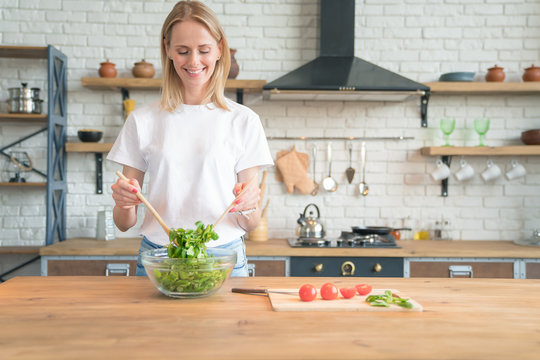 beautiful young smiling woman making salad in the kitchen. Healthy food. vegetable salad. Diet. Healthy lifestyle. cooking at home. Wearing white shirt and jeans.