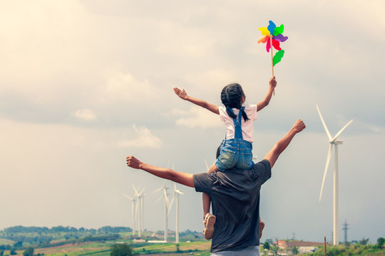 Father and daughter having fun to play together. Asian child girl playing with wind turbine and riding on father's shoulders in the wind turbine field