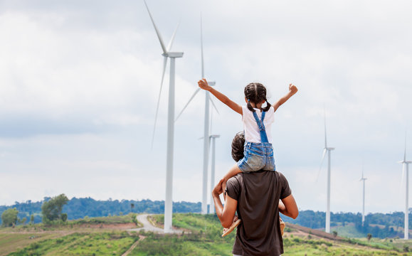Father and daughter having fun to play together. Asian child girl riding on father's shoulders in the wind turbine field